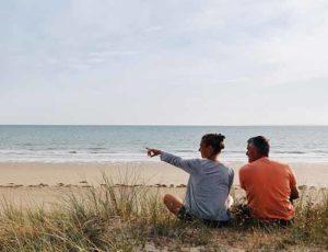 Un couple assis dans les dunes à Bretteville-sur-Ay