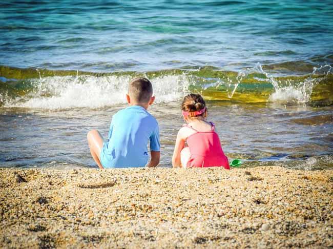 Des enfants jouant sur la plage en période estivale
